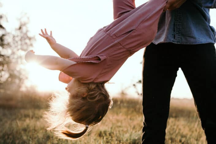 Dad is throwing his little girl in the air. family lifestyle photography in Basongstoke, Hampshire. Ewa Jones Photography