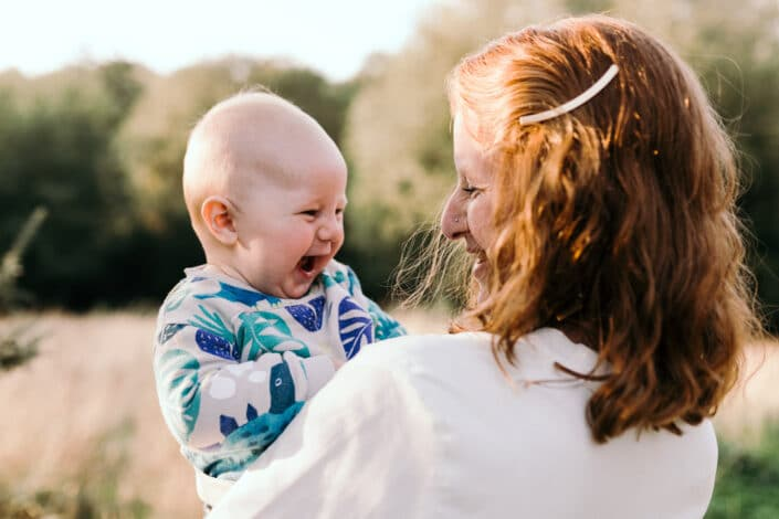 Mum is looking at her baby boy and laughing to him. Boy is laughing back at his mum. Lovely candid photograph of mum and son love. Family photographer in Hamsphire. Ewa Jones Photography