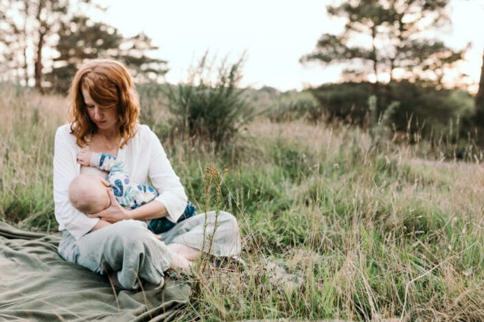Mum is sitting on the blanket and breastfeeding her little boy. Lovely sunset photography in Hampshire. Family photography in Hampshire. Ewa Jones Photography