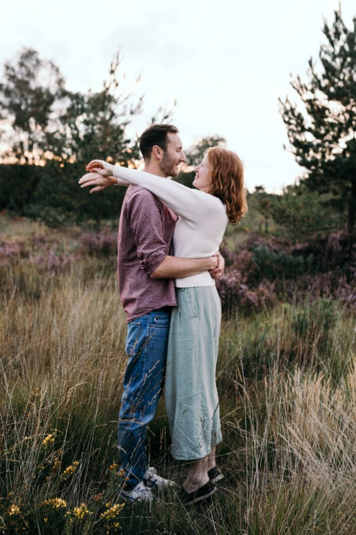 Husband and wife are holding each other. Wife is on her toes and has wrapped straight arms around her husband. Lovely couple photography in Hampshire. Ewa Jones Photography