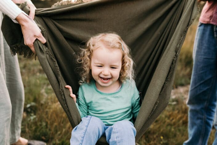 Little girl is sitting inside the green blanket and laughing. Family photography in Hampshire. Ewa Jones Photography