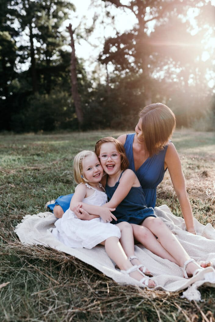 Mum and two daughters sitting on the blanket in the field hugging each other and smiling. Natural family portraits photography in Basingstoke. Hampshire. Ewa Jones Photography