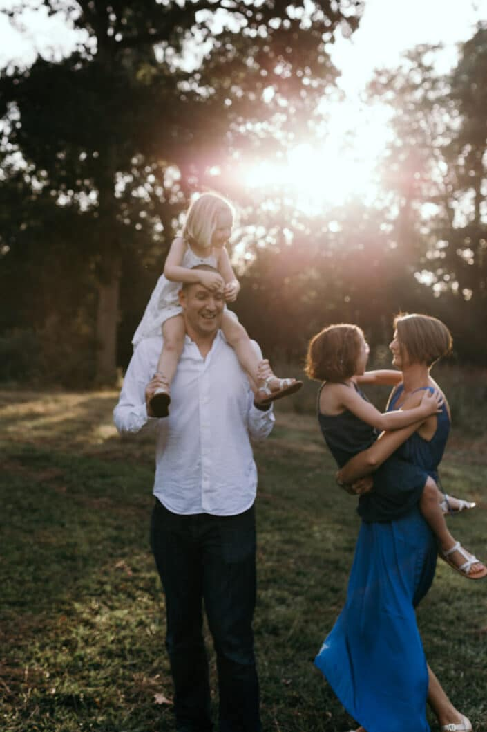 Family fun, dad has a girl on his shoulders and mum is dancing with daughter. Natural family portraits in Hampshire. Ewa Jones Photography