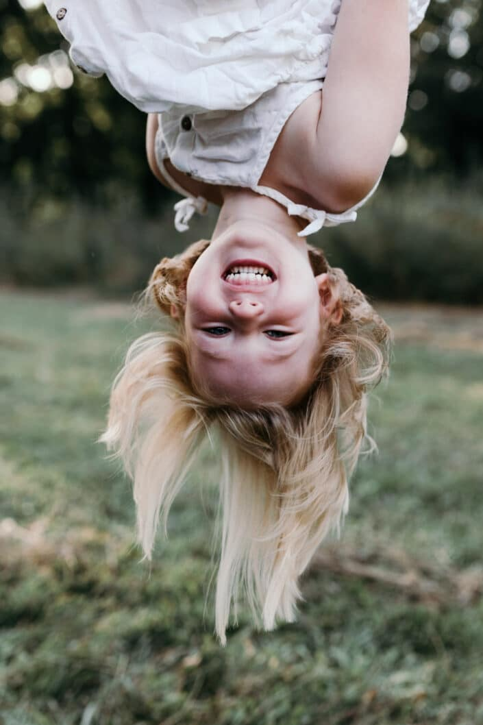 Girl upside down laughing in the field. Natural family lifestyle photoshoot in Hampshire, Ewa Jones Photography