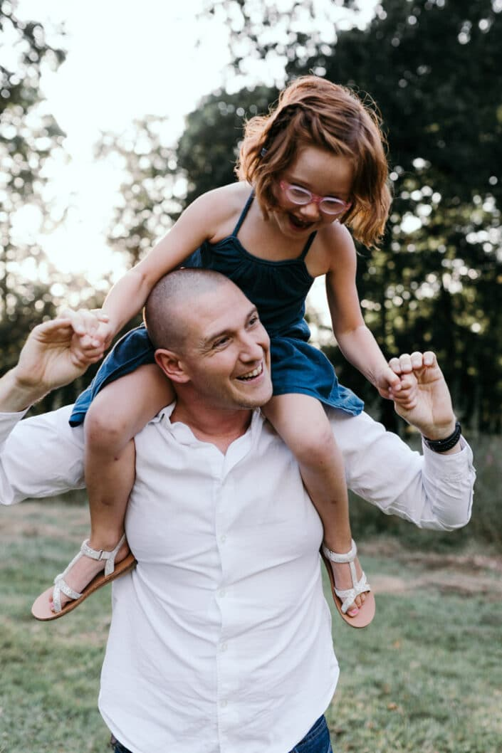 Daughter is on daddy's shoulders and laughing. Shoot in front of the sun back lit. Natural family photoshoot in Hampshire. Ewa Jones Photography