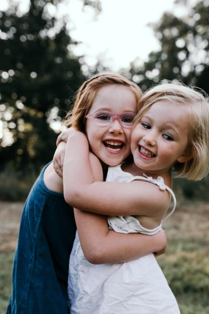 Sisters hugging and laughing. Family photoshoot in Hampshire   Ewa Jones Photography