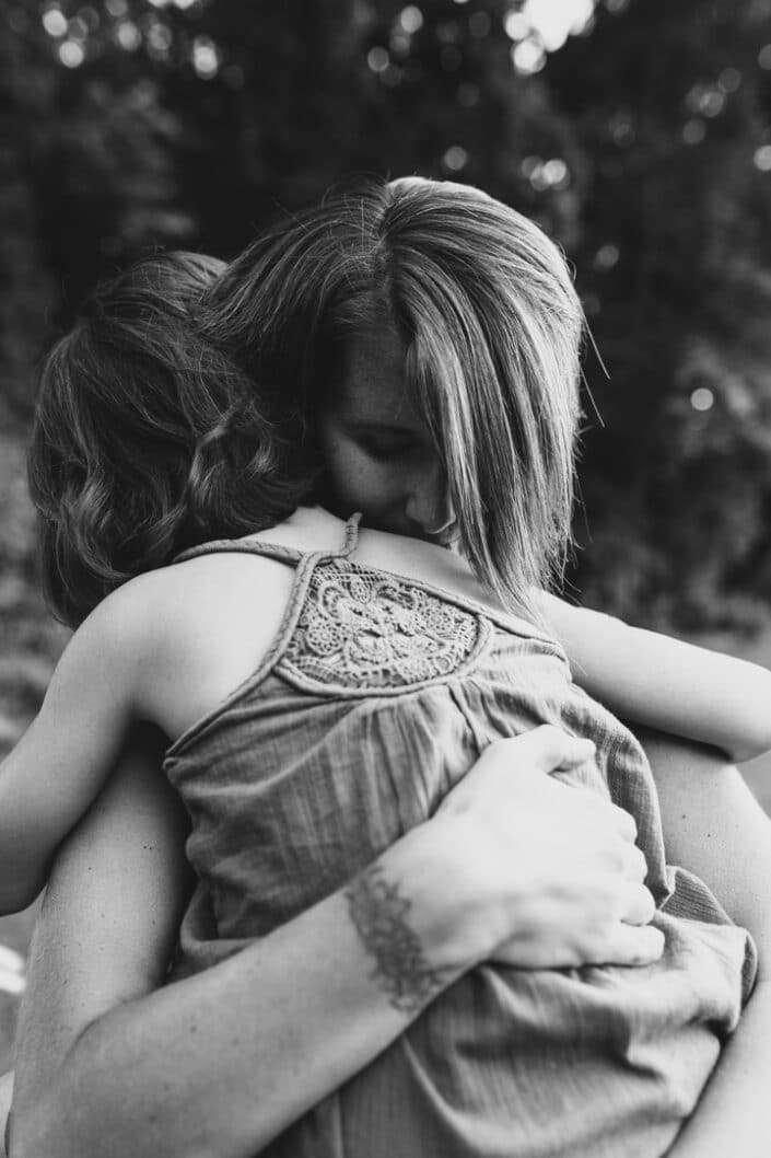 Mum is holding her daughter and daughter is cuddling to her mum. Vogue published photograph. Family photographer in Hampshire. Ewa Jones Photography