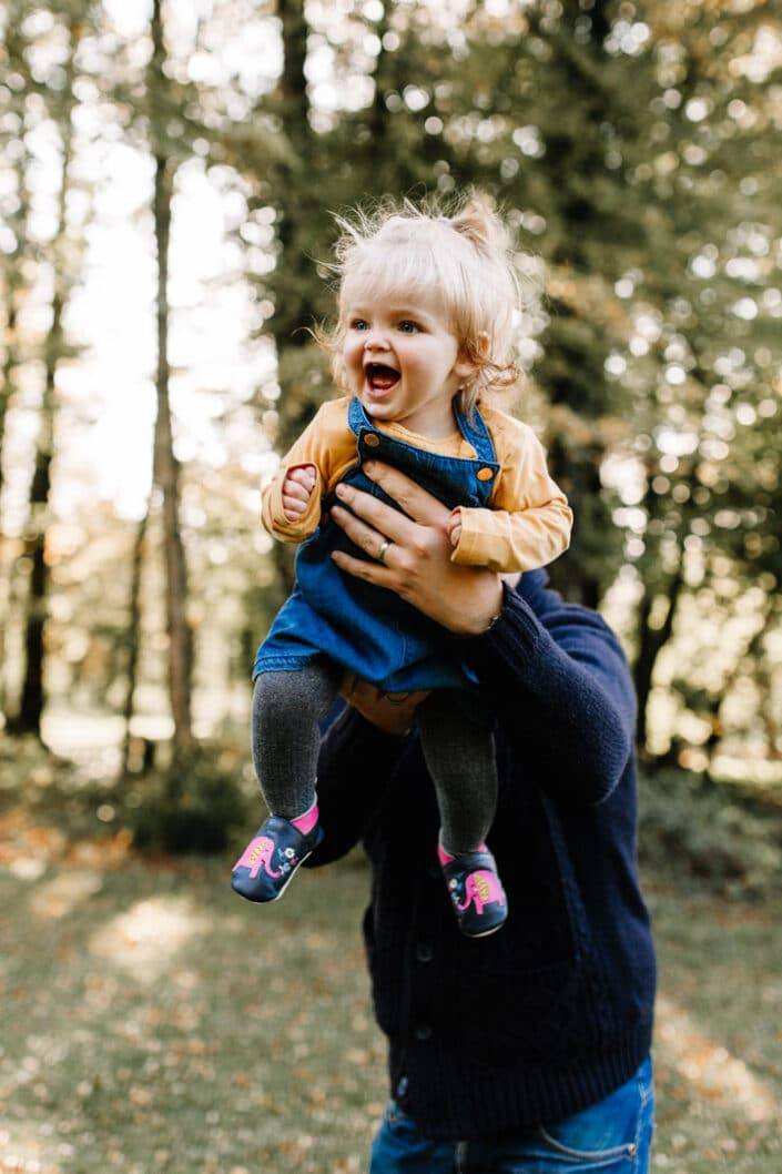 Dad is swinging his little girl high in the air. Autumn family photo shoot in Hampshire. Family photography in Hampshire. Ewa Jones Photography