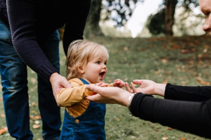 Little girl is trying to walk and holding her hands and walking towards mummy. Lovely family autumn photo session in Hampshire. Family photographer in Hampshire. Ewa Jones Photography