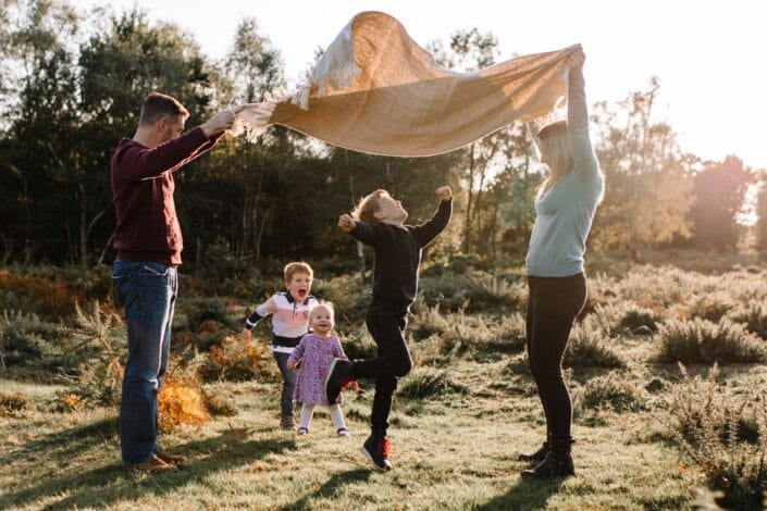 Mum and dad are holding a blanket and lifting it in the air. Three children are running through the blanket. Autumn family photo session in Hampshire. Ewa Jones Photography