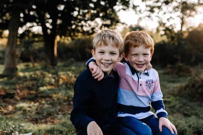 Two brothers are sitting on the log and looking at the camera. They are both giggling. One boy is wearing blue jumper and one is wearing stripy top. Autumnal family photo session in Hampshire. Family photographer in Hampshire. Ewa Jones Photography