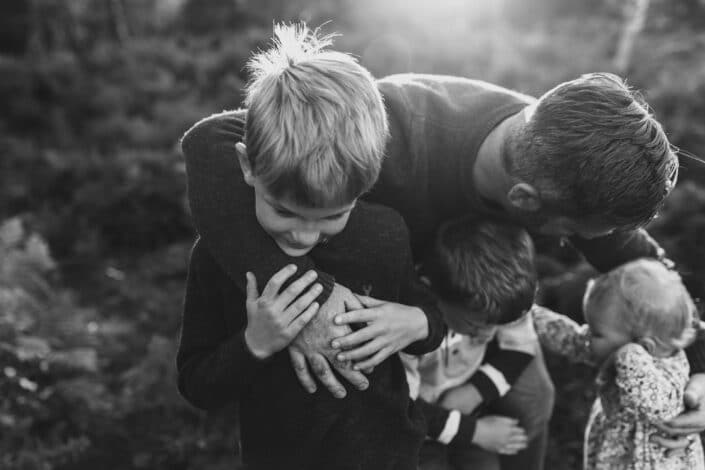 Black and white photograph of dad holding his three children. Candid close up shoot of son holding dads hand. Lovely family lifestyle photography in Hamsphire. Ewa Jones Photography