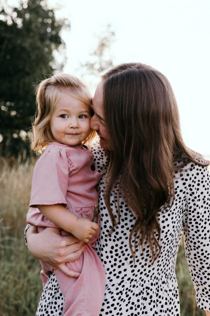 Mum is standing and holding her daughter. she is smiling to her. Mum is wearing lovely white dress with black dots and girl is wearing pink jump suit. Family lifestyle photography in Basingstoke, Hampshire. Ewa Jones Photography