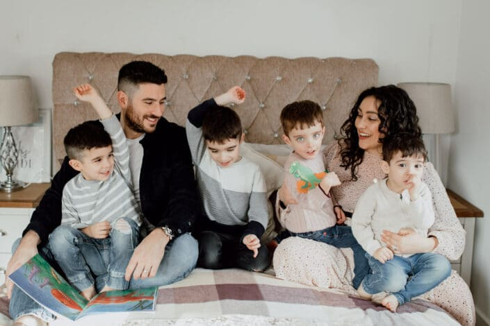 Family of six is sitting on the bed and looking at each other. They are all laughing. Family lifestyle photo session in Hampshire. Ewa Jones Photography