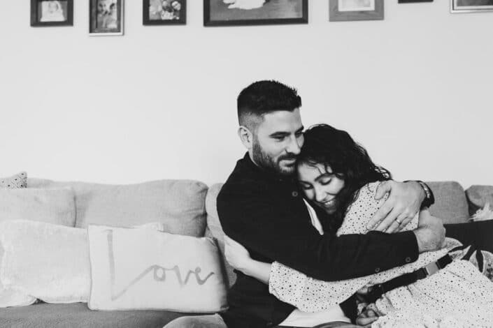 Black and white candid photograph of wife and husband sitting on the sofa and cuddling to each other. Beautiful couple photography in Hampshire. Ewa Jones Photography