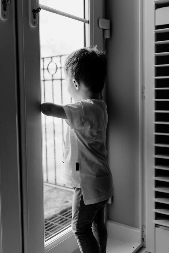 Black and white photograph of little boy looking through the window. Family in home lifestyle photography in Basingstoke. Ewa Jones Photography