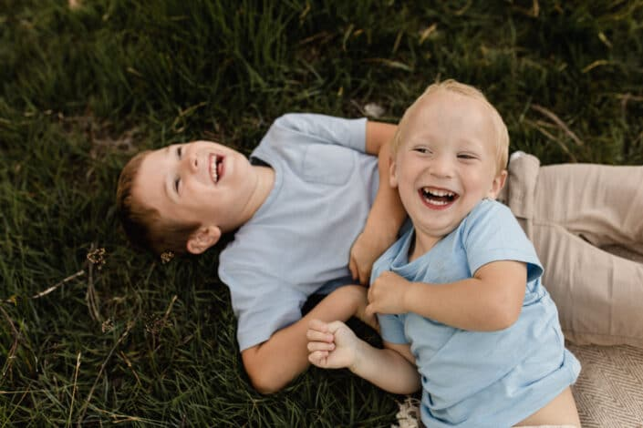 Two brothers are laying on the grass and laughing. Both boys are wearing blue t-shirts. Lovely family photography in Hook, Hampshire. Ewa Jones Photography