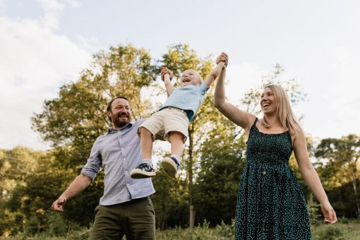 Mum and dad are lifting little boy up in the air. Golden hour photo session in Hook, Hampshire. Ewa Jones Photography