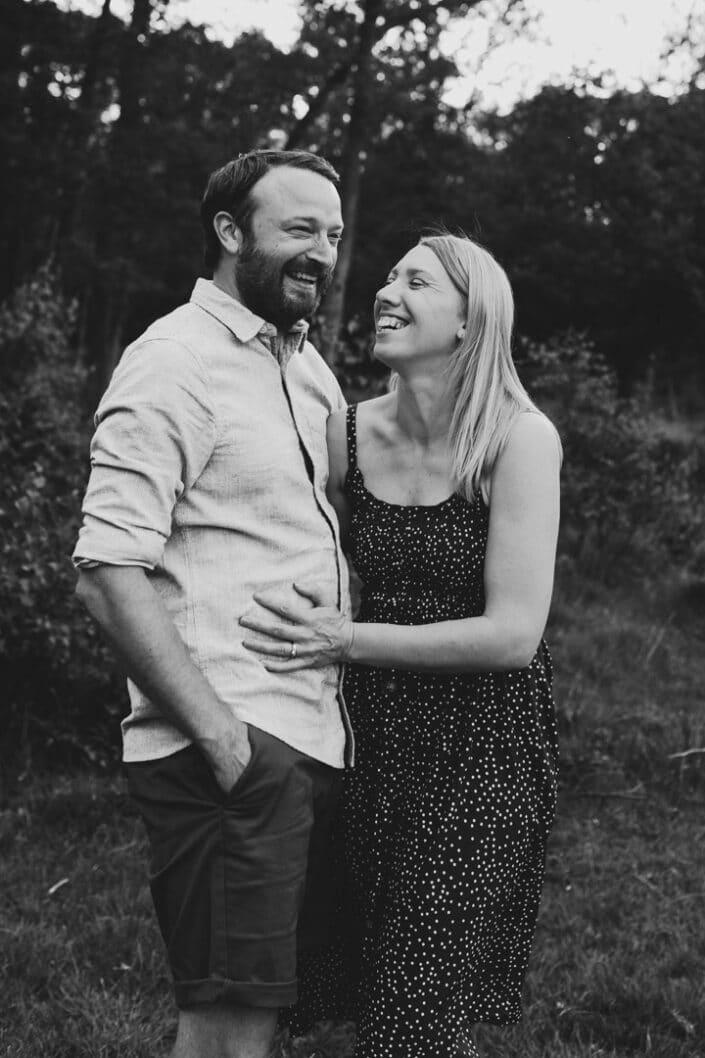 Black and white photograph of mum and dad holding and laughing. Lovely couple photograph in hook, Hampshire. Ewa Jones Photography