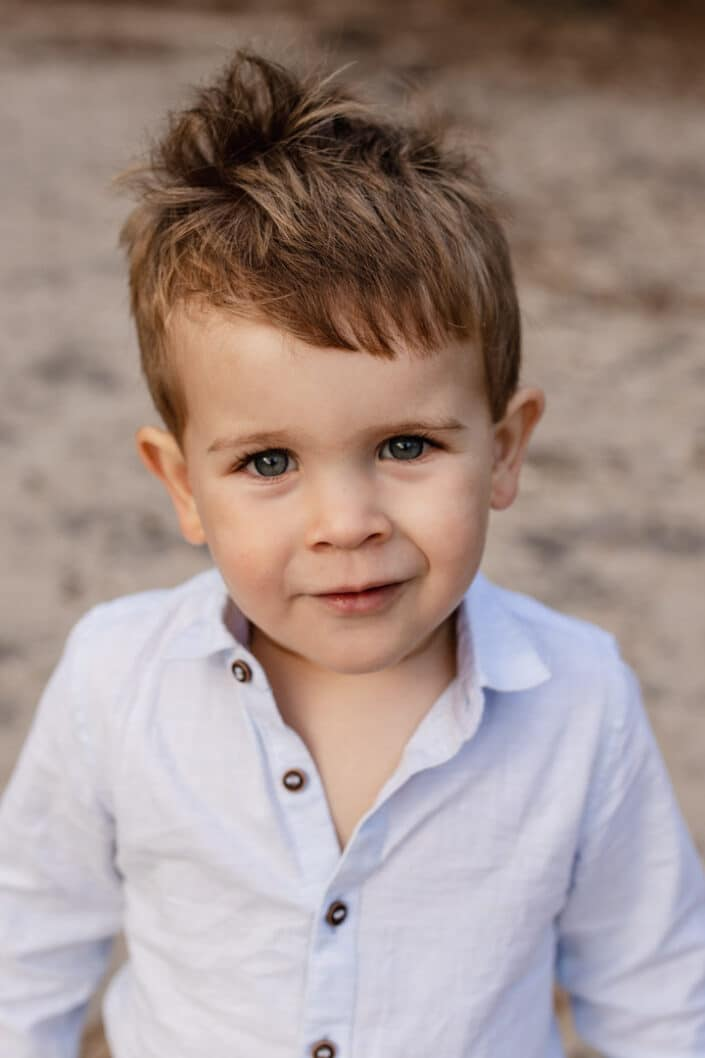Little boy is looking straight at the camera with his lovely blue eyes. He is wearing lovely light blue shirt. Golden hour photo session in Frensham. Family photography in Hamsphire. Ewa Jones Photography