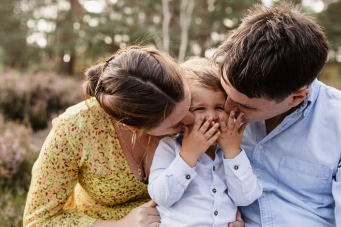Mum and dad are kissing their little son on his cheeks. Boy is covering his mouth with his hands and is giggling. Family lifestyle photo session in Hampshire. Ewa Jones Photography