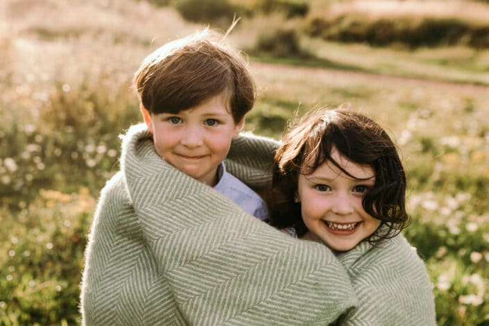 Little sister and her brother are both looking at the camera. they are very cheeky and are wrapped in the green blanket. Family photo session in Basingstoke. Ewa Jones Photography