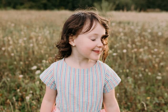 Little girl has her eyes closed and her little hair has flicked onto her eye. Lovely candid and emotional photograph. Family photographer in Hampshire. Ewa Jones Photography