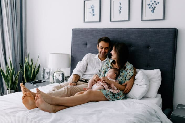 Mum, dad and their little baby girl are sitting on the bed. Mum and dad are looking lovingly at each other. Lovely natural family photography in Hammersmith. Ewa Jones Photography