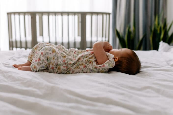 Little baby girl is laying on the bed and looking away. Baby cot in the background. Baby girl is wearing flower body. Family photography in London. Ewa Jones Photography