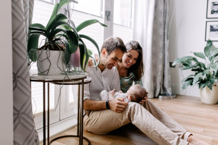 Mum and dad are sitting on the floor and looking at their baby girl. There are plants in front of them and lovely light coming from the outside. Natural photography. Ewa Jones Photography