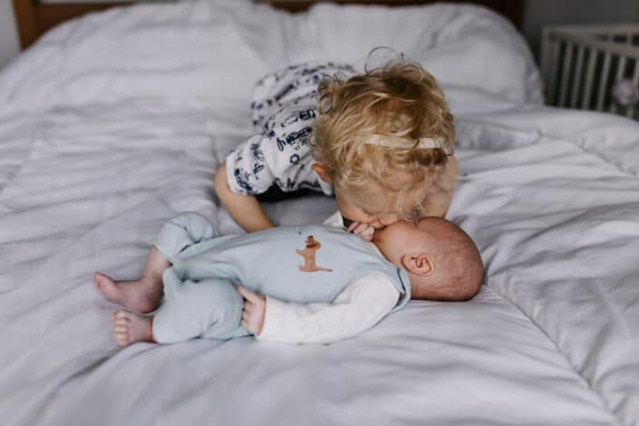Older brother is kissing his little baby brother. Lifestyle newborn baby photography. Newborn baby photography in Reading, Berkshire. Ewa Jones Photography