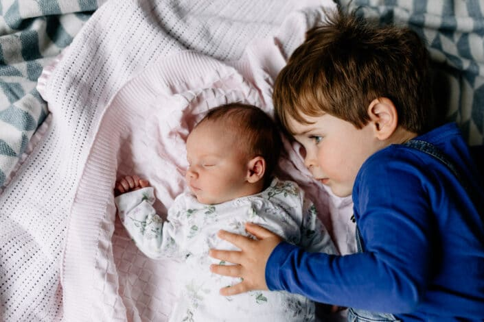 Little baby girl is laying on the blankets and sleeping. Her older brother is looking at her and holding his hand on her chest. Lovely lifestyle newborn baby photography in Hampshire. Ewa Jones Photography