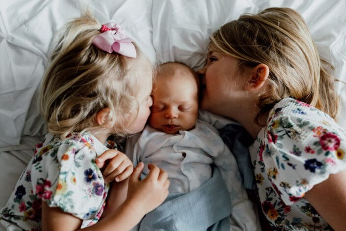 Two sisters are laying on the bed and kissing their baby brother. Girls are wearing lovely flower dresses and baby boy is wearing baby grow. Natural unposed newborn baby photography in Basingstoke, Hampshire. Ewa Jones Photography