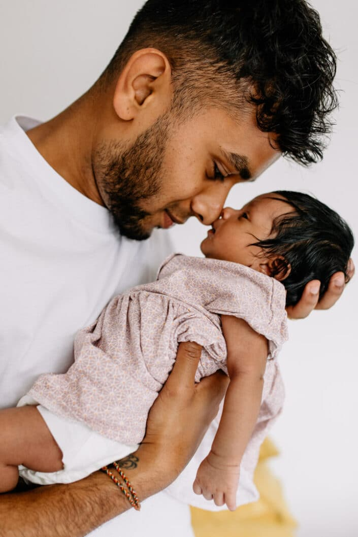 dad is holding his newborn baby girl close to his face. lovely candid moment between new dad and his baby girl. Newborn baby is wearing lovely pink dress. Newborn photographer in London. Ewa Jones Photography