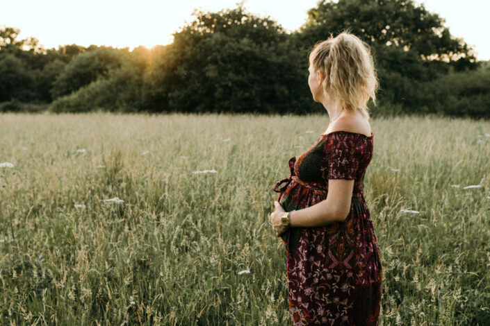 Pregnant mum is standing in the long grass and looking into the sun. Maternity photo shoot during sunset. Ewa Jones Photography