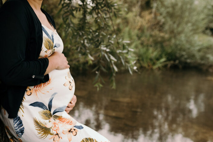 Mum is standing and holding her bump. Maternity photo session in Basingstoke. Ewa Jones Photography