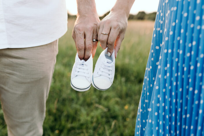 Expecting parents are holding tiny baby white shoes. Lifestyle maternity photography in Hampshire. Ewa Jones Photography