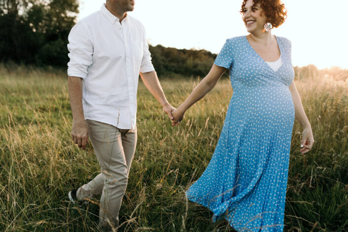 Expecting parents are holding hands. Wife is first and looking back at her husband and smiling to him. Maternity photo session in Hampshire. Ewa Jones Photography