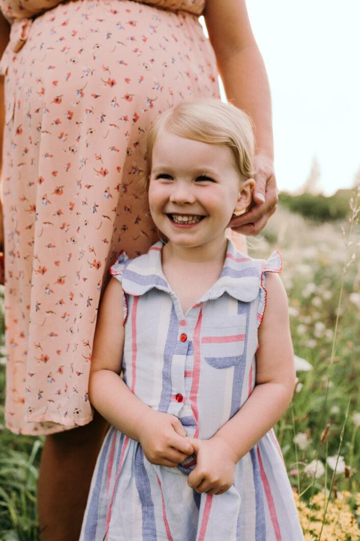 Little girl is standing and smiling. She is wearing a stripy dress. Pregnant mum is standing behind her and touching her hair. Maternity and family photography in Basingstoke. Ewa Jones Photography