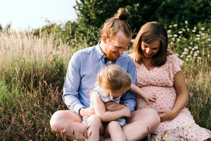 Parents and little girl are sitting on the grass. Little girl is touching her mum bump. Maternity and family photographer in Basingstoke. Ewa Jones Photography