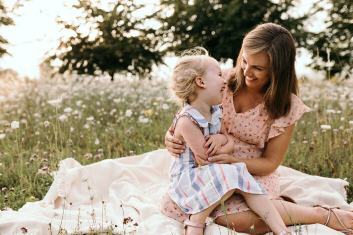 Mum and daughter are sitting on the blanket and laughing at each other. Lovely candid photo. Sunset maternity and newborn photography in Hampshire. Ewa Jones Photography