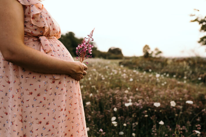 Pregnant mum is wearing a lovely dress and holding pink flowers. She is standing on a lovely field. Maternity photographer in Hampshire. Ewa Jones Photography