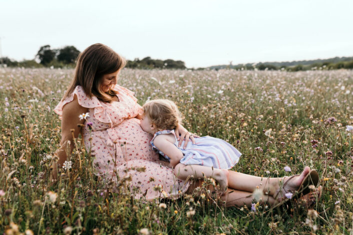 Little girl is kissing mummy bump. Lovely mum and daughter moment. Family and maternity lifestyle photography in Basingstoke. Ewa Jones Photography