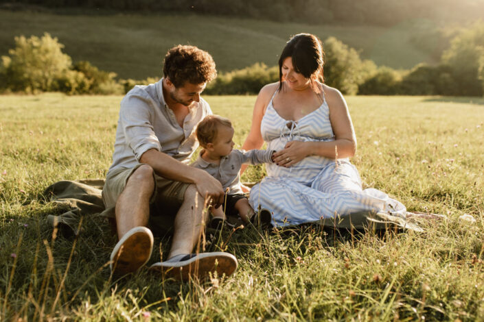 Lovey sunset maternity photo session. Parents are sitting on the grass and their little boy is touching bump. Maternity photo session in Hampshire. Ewa Jones Photography