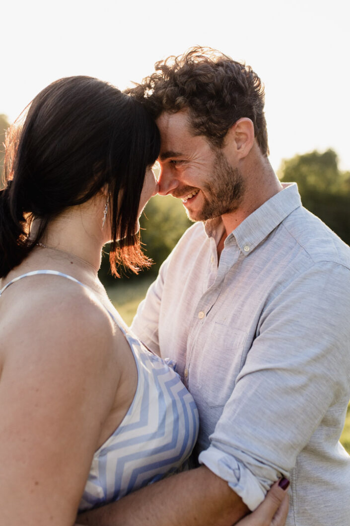 Dad is looking lovingly at his partner. Both are touching foreheads and smiling to each other. Sunset maternity photo session. Ewa Jones Photography