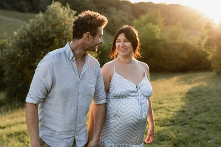 Parents to be are holding hands and looking at each other. They are walking and the lovely sunset is behind them. Natural lifestyle maternity photography in Hampshire. Ewa Jones Photography