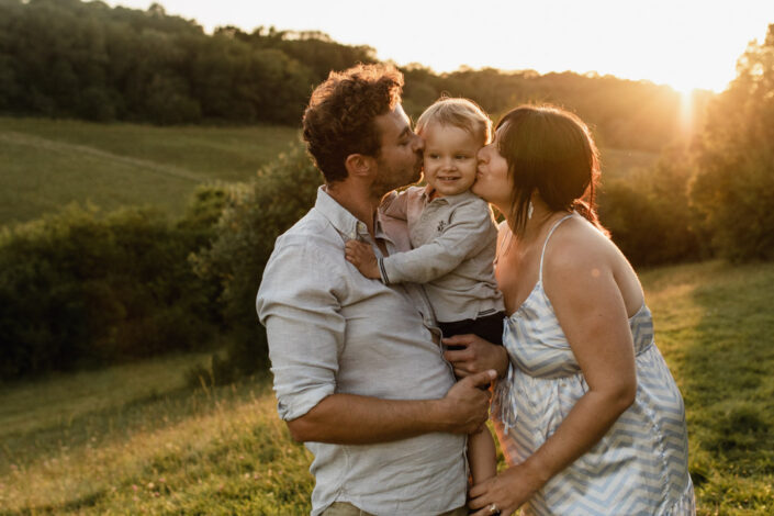 Mum and dad are kissing their toddler. Family and maternity photography in Hampshire. Ewa Jones Photography