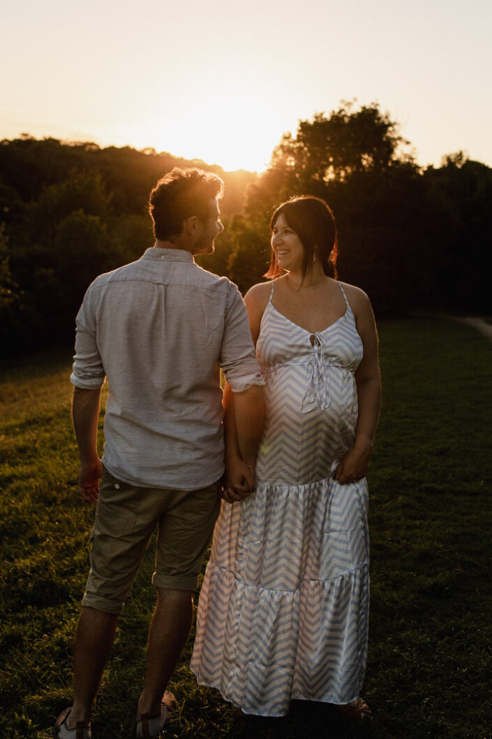 Mum and dad are standing in front of the sunset. They are lovingly looking at each other. Lovely maternity photo session. Ewa Jones Photography