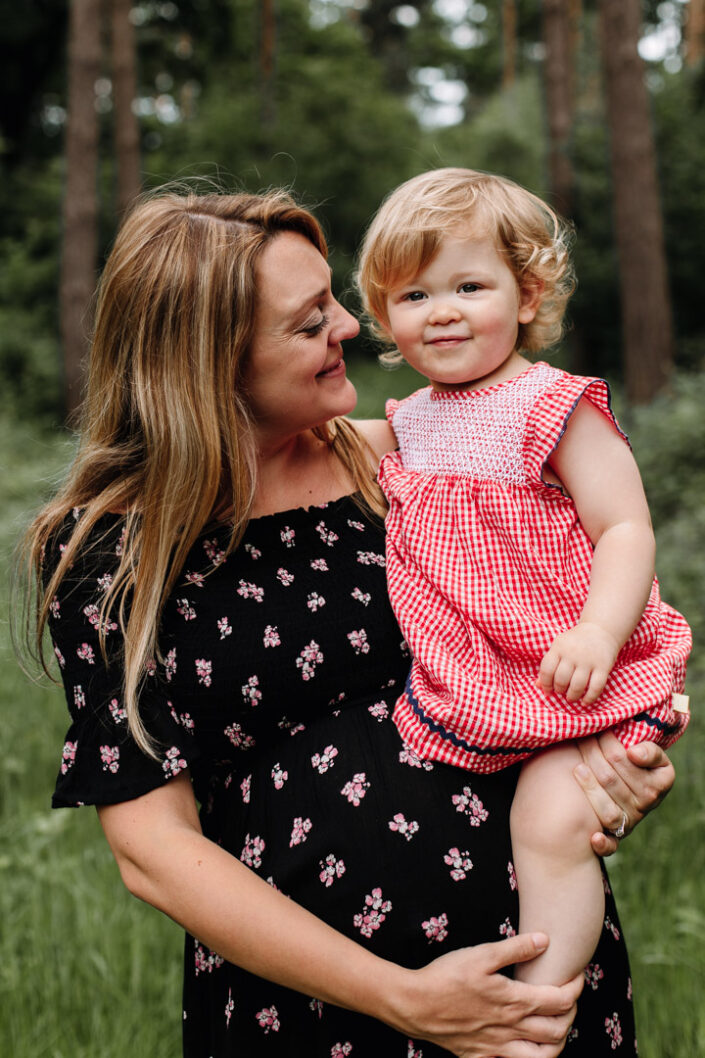 Mum is holding her toddler girl and looking at her. Lovely maternity photo shoot in Basingstoke. Ewa Jones Photography
