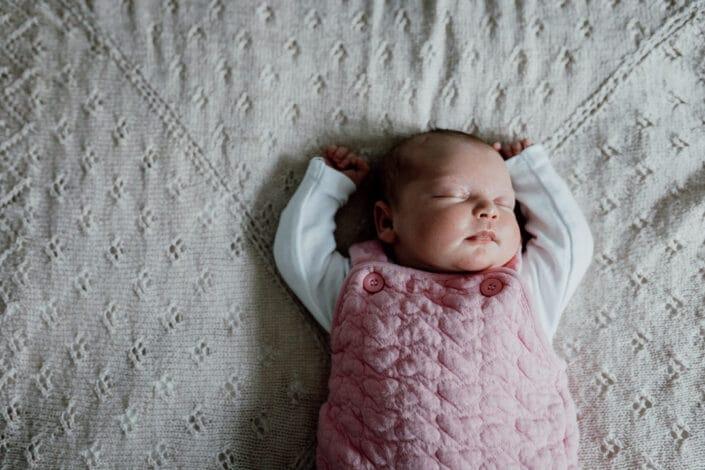 Newborn baby sleeping on the bed with hands up. Hampshire newborn photoshoot. Newborn photographer in Basingstoke. Ewa Jones Photography